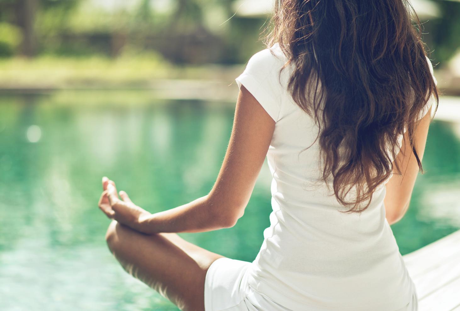 A woman meditating in front of a Bangsar lake.