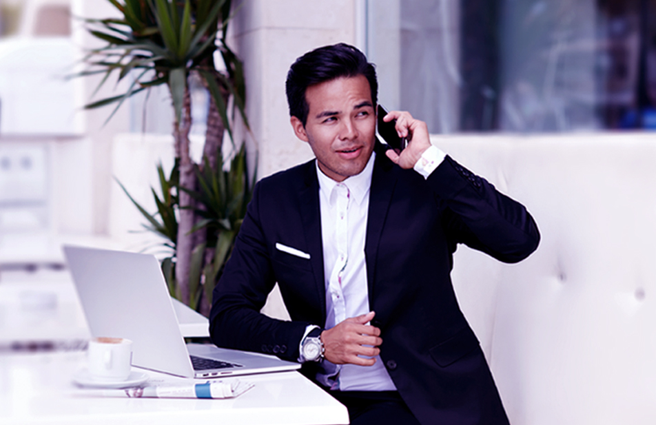 A man in a suit sitting at a cafe while calling on a phone