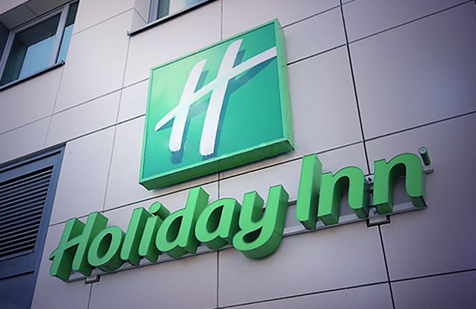 Holiday Inn logo on a building wall.